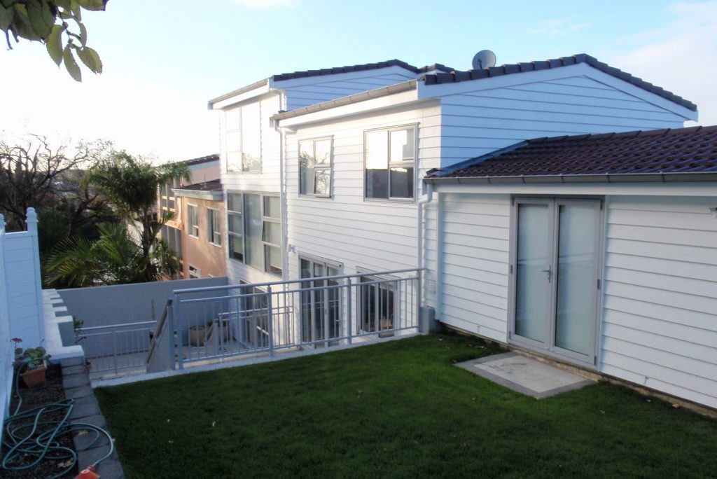 the rear of a weatherboard property after renovation with multi-level outdoor spaces.