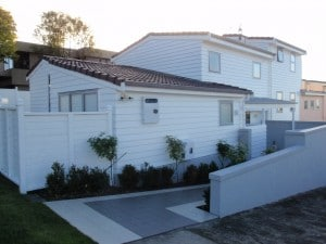 a recently renovated weatherboard house with a tiled roof and with a tiled pathway to the door and a line of planting along the wall.