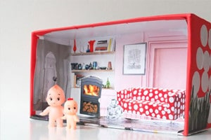 toy dolls in a toy shoebox house