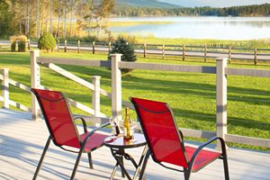 two red outdoor chairs and a table with drinks on it set on a deck looking out across a fence to a grass section with a lake beyond