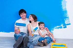 a dad, mum and boy holding paint rollers leaning against a wall which is partly painted blue