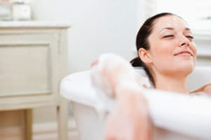a woman in a bubble bath looking very relaxed in a renovated bathroom