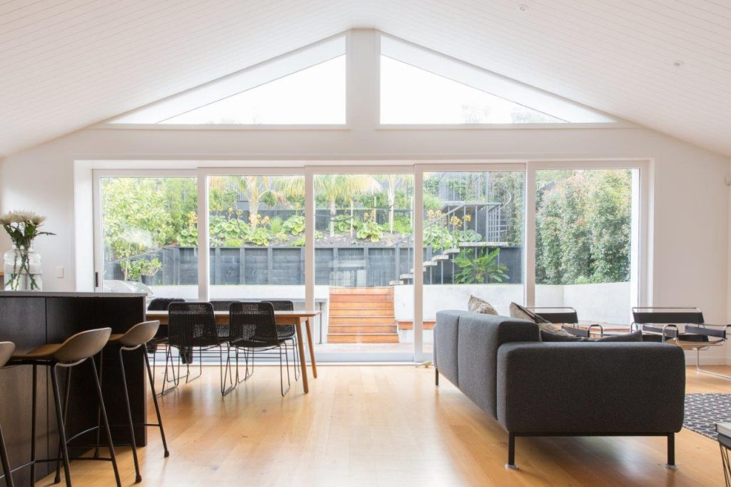 Lounge with full glass windows to ceiling, showing lots of light streaming into room with a rear house extension