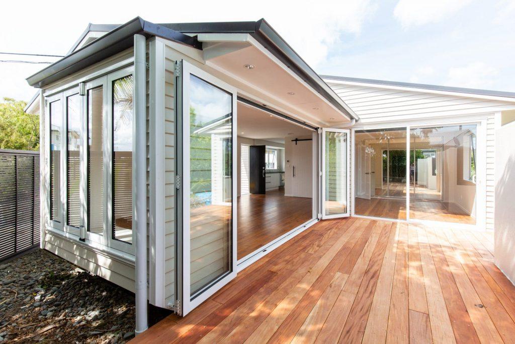 a wooden outdoor deck with large patio doors leading inside for great indoor outdoor flow