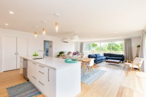a view of an open plan kitchen and living area with kitchen island and sofas