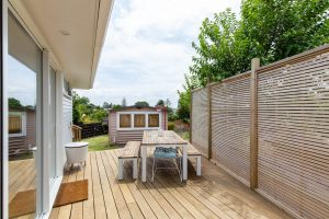 a wooden outdoor deck with patio furniture and fencing