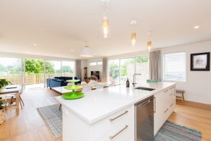 A renovated house with a kitchen unit looking out onto an open plan dining and living area