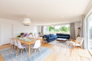 Renovated dining and living space with a dining table and sofas and wooden floors