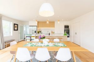 a view of a dining table and chairs looking towards an open plan kitchen