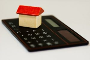 a wooden model house on top of a calculator being used to work out budgeting for a house extension
