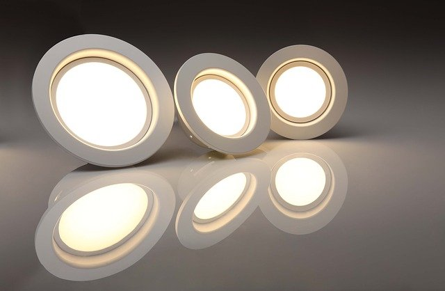 three energy efficient led lightbulbs in casings reflected on a surface